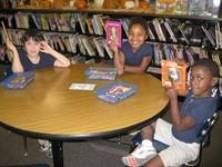 Three TCS students holding up library books